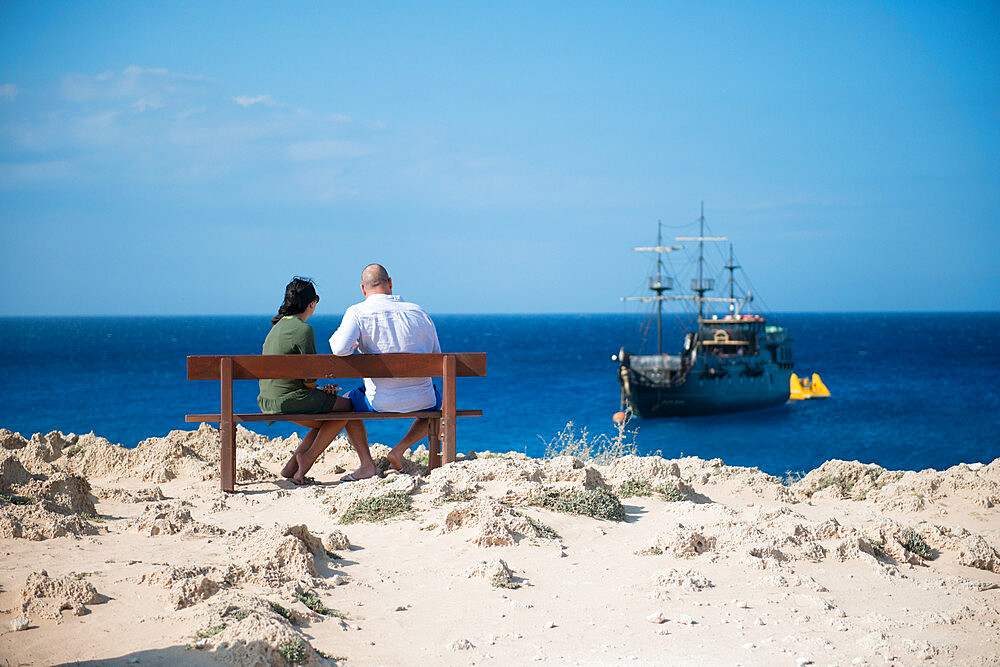 Couple sat overlooking a themed pirate ship, Cape Greco, Protaras, Cyprus, Mediterranean, Europe