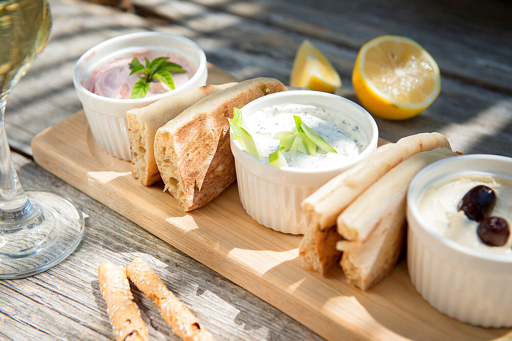 Meze at a Cypriot restaurant of Taramasalata, tzatziki, hummus, pitta bread, lemon and olives accompanied with white wine, Cyprus, Mediterranean, Europe - 1331-54