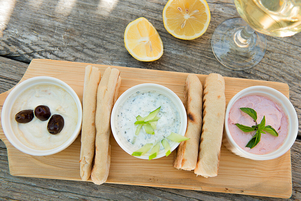 Meze at a Cypriot restaurant of Taramasalata, tzatziki, hummus, pitta bread, lemon and olives accompanied with white wine, Cyprus, Mediterranean, Europe