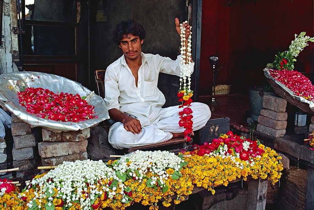 Portrait of a man selling garlands of flowers in the flower market in Lahore, Punjab, Pakistan, Asia