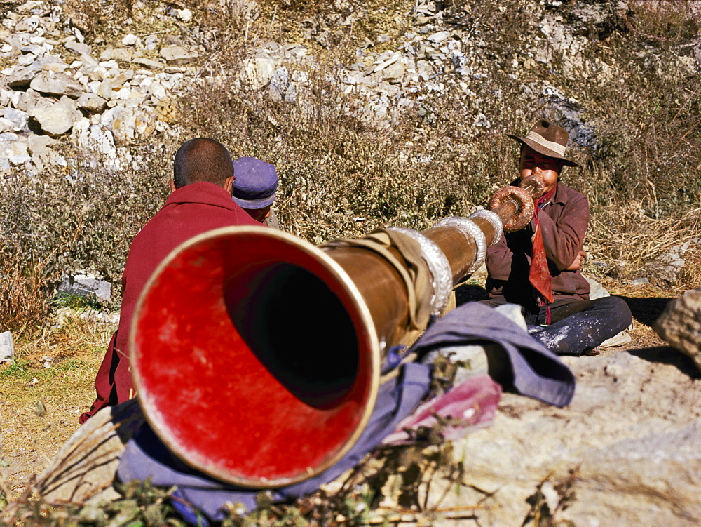 Blowing giant horn at Ganden Monastery, Tibet, China, Asia - 16-3290