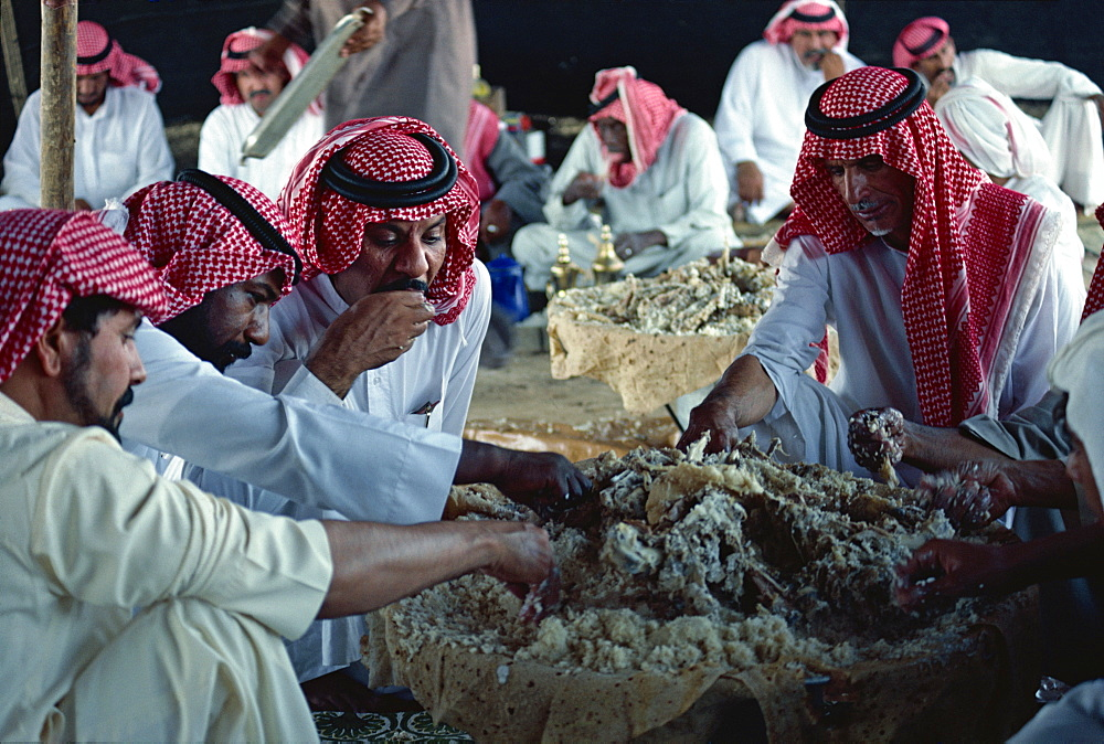 Group of men eating at a Bedouin feast, Saudi Arabia, Middle East