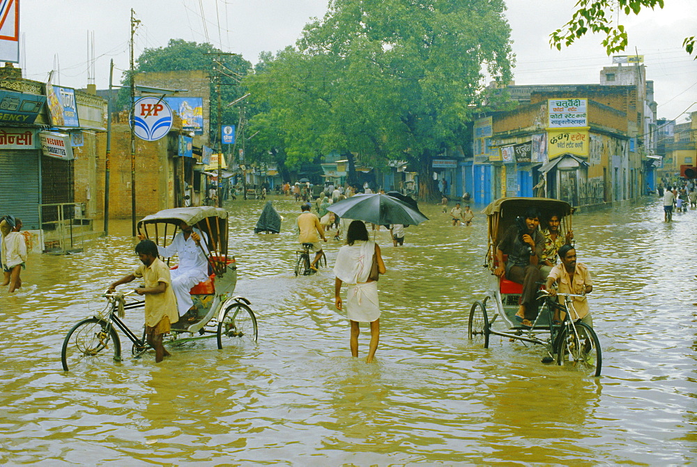 Rickshaws being pushed through the monsoon floods in a town, India