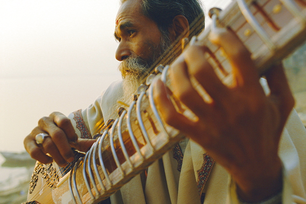 Stock photo of Elderly man playing the sitar beside the Ganges