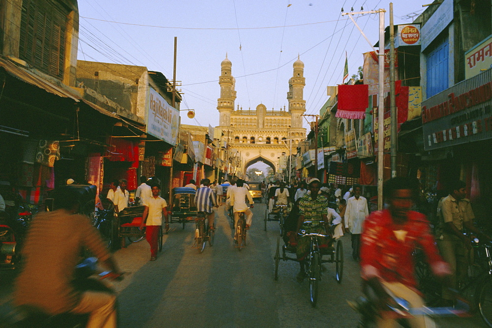 Street scene with bicycles and rickshaw and the Char Minar (Charminar) triumphal arch built in 1591, Hyderabad, Andhra Pradesh State, India