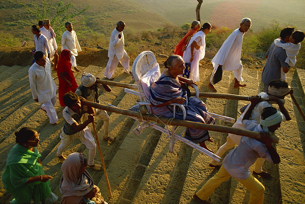 Jain pilgrims walking and being carried up the sacred hill of Palitana, Gujarat state, India, Asia
