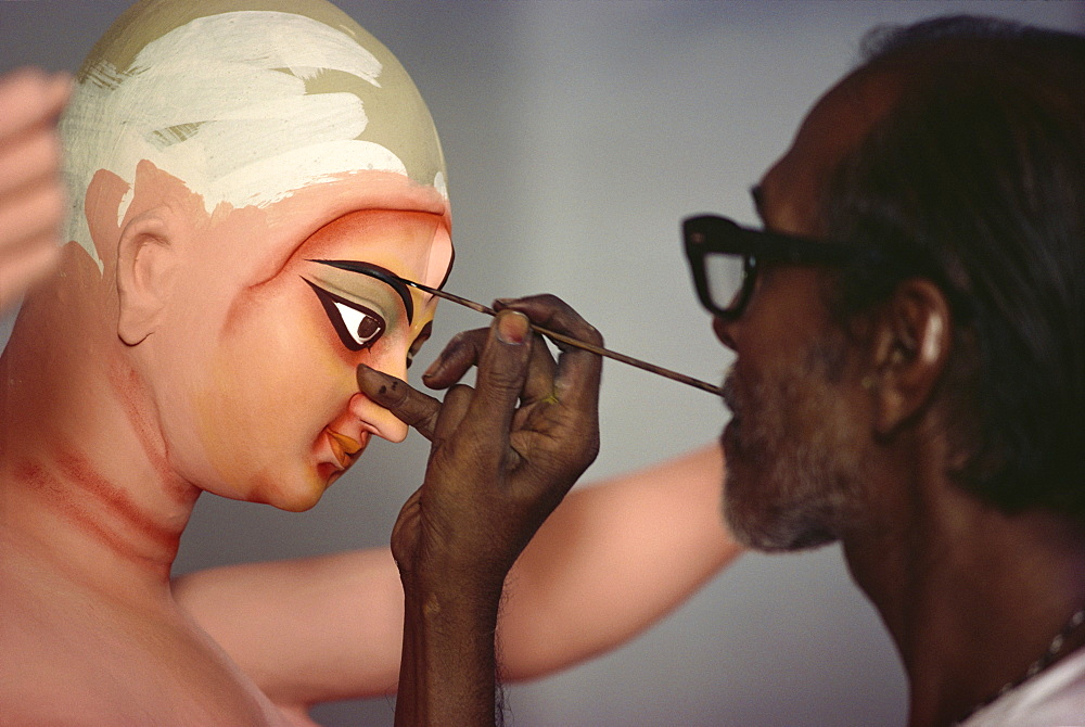 Painting clay based image of Durga, the ten armed warrior goddess, for use in the Durga Puja festival, Varanasi, Uttar Pradesh, India, Asia