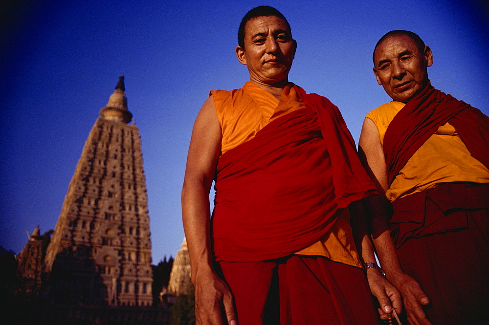 Two Tibetan monks with the main Mahabodhi temple in the background, Bodh Gaya, Bihar state, India, Asia