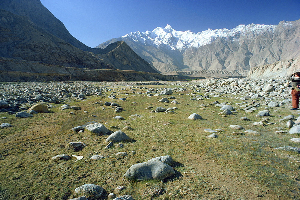 Rocky valley with snow capped mountains in the background on the Karakorum Highway on route to Pakistan, in Xinjiang Province, China, Asia
