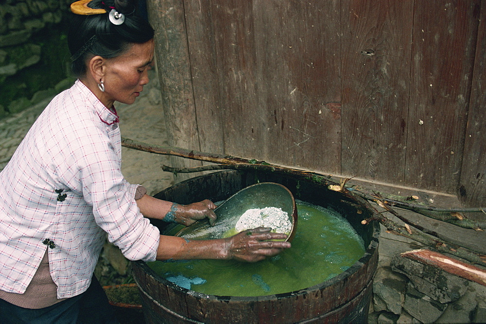 Lime being added to indigo paste, Guizhou, China, Asia