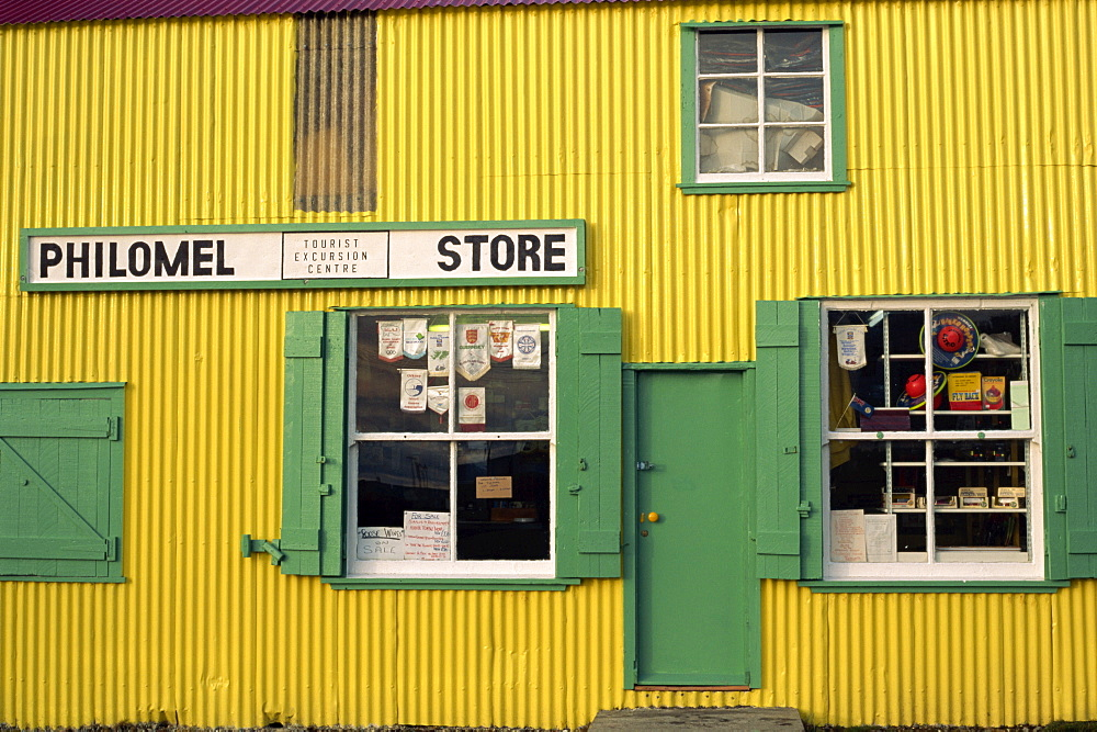 Brightly painted yellow corrugated wall and green wooden building of the general store selling hardware and gifts, Stanley, Falkland Islands, South America