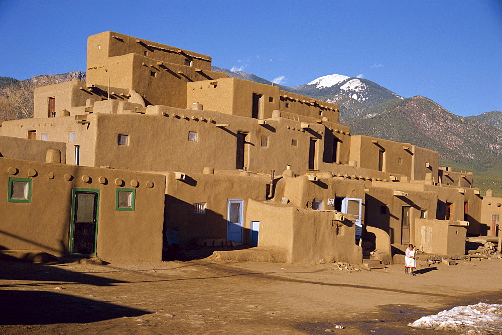 Woman sweeping up, in front of the adobe buildings of the north complex, dating from 1450, Taos Pueblo, UNESCO World Heritage Site, New Mexico, United States of America, North America