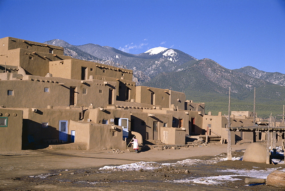 Lady sweeps up after visitors have departed, multistorey adobe buildings in north complex dating from around 1450 AD, Taos Pueblo, UNESCO World Heritage Site, Taos, New Mexico, United States of America (U.S.A.), North America