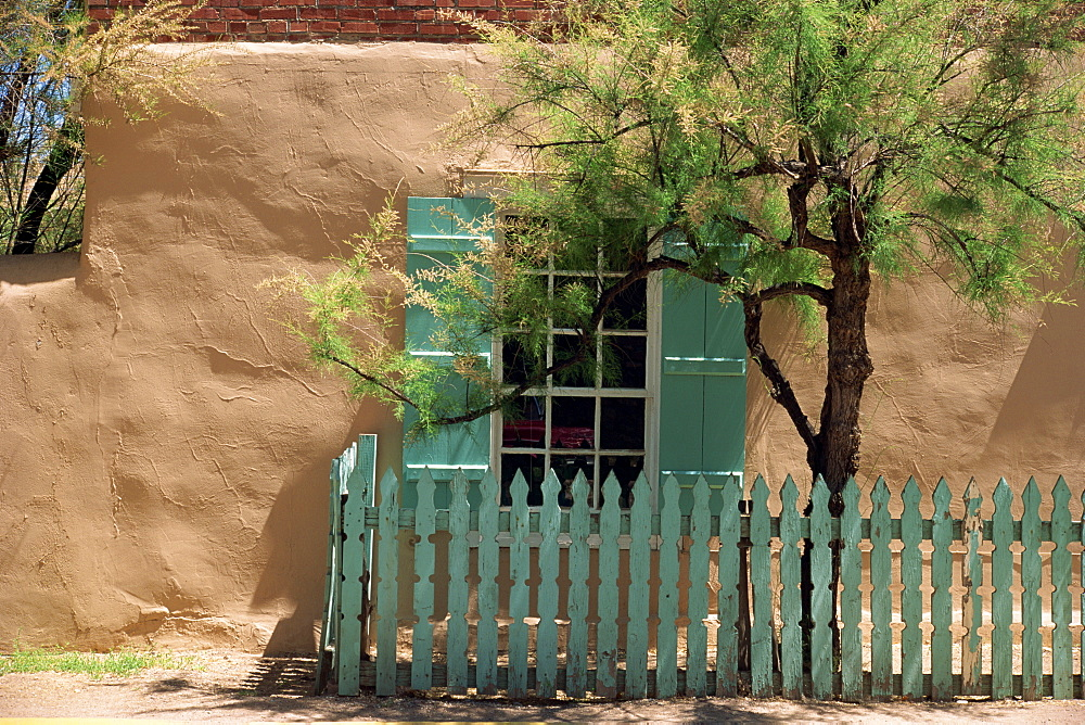 Detail of old adobe house with turquoise shutters and picket fence which traditionally bring good luck, Santa Fe, New Mexico, United States of America, North America