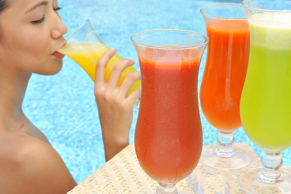 Young woman in a swimming pool sipping one of a selection of fruit juices - 238-5080