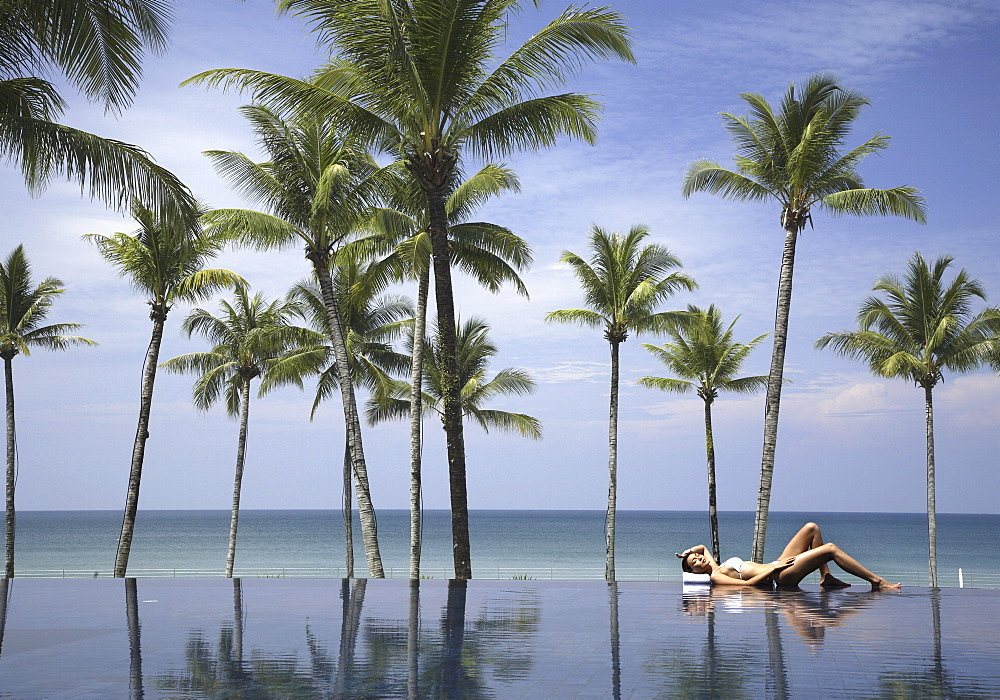 Young woman relaxing by pool with palm trees and the sea beyond