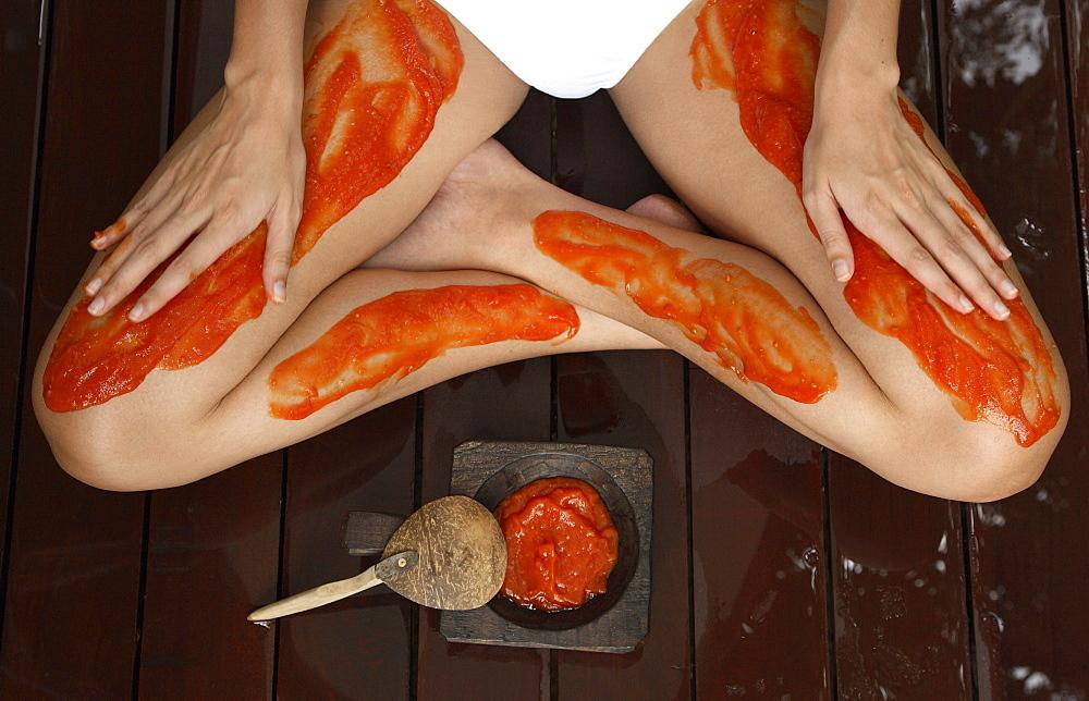 Close-up of papaya and tamarind scrub treatment on legs