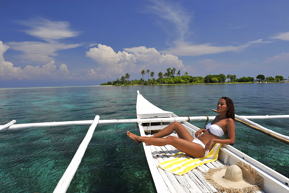 Girl on a traditional boat and the islet off the coast of Bohol, Philippines, Southeast Asia, Asia