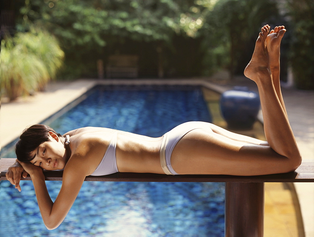 Woman relaxing by the pool - 238-5886