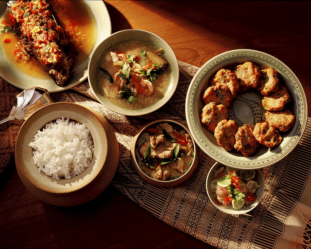 A typical Thai meal balancing spicy, sour and sweet flavours, consisting of spicy thom yam soup, weet and sour fish, fish patties, a curry dish and rice, Thailand, Southeast Asia, Asia
