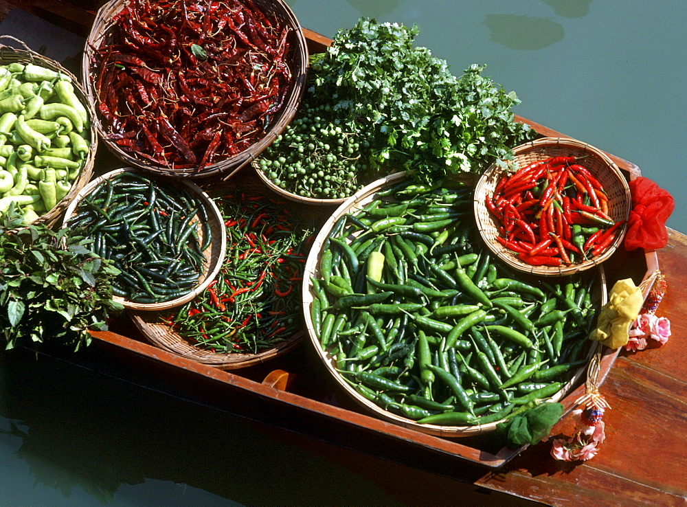An assortment of chillies, a staple ingredient of Thai cooking, on sale on a boat in a floating market in Thailand, Southeast Asia, Asia