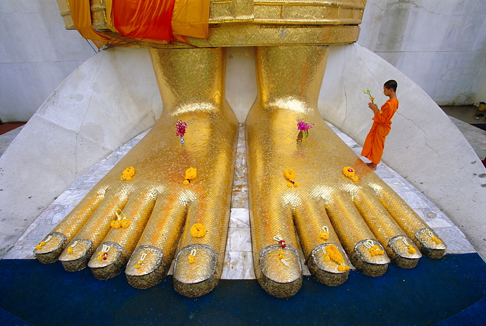 Novice monk praying at the feet of Giant Buddha statue, Wat Intharawihan (Wat In), Bangkok, Thailand, Asia - 252-10008