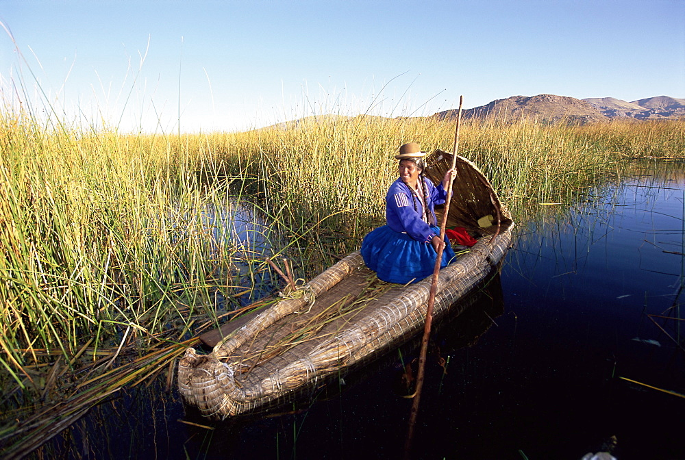 A Uros Indian woman in a traditional reed boat, Islas Flotantes, floating islands, Lake Titicaca, Peru, South America