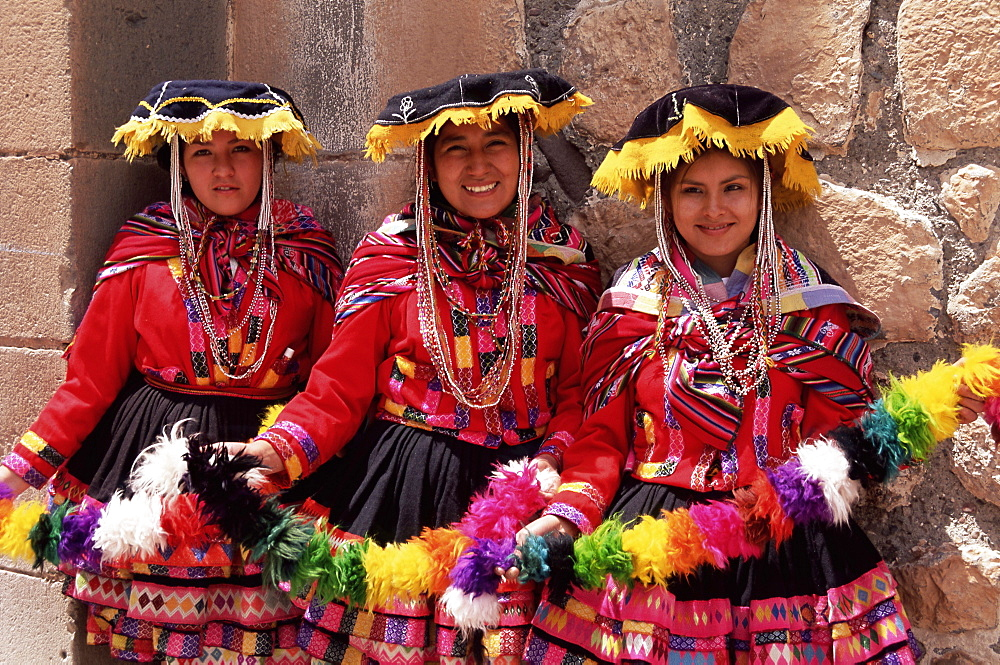 Portrait of three smiling local Peruvian girls in traditional dance dress, smiling and looking at the camera, Cuzco, Peru, South America