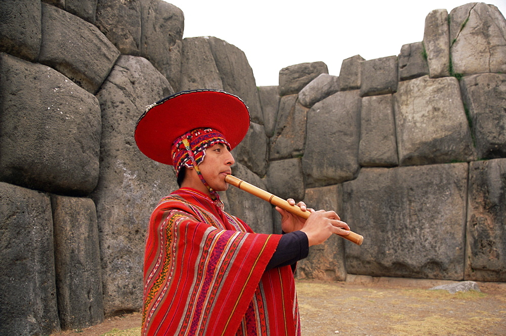 Portrait of a Peruvian man playing a flute, Inca ruins of Sacsayhuaman, near Cuzco, Peru, South America