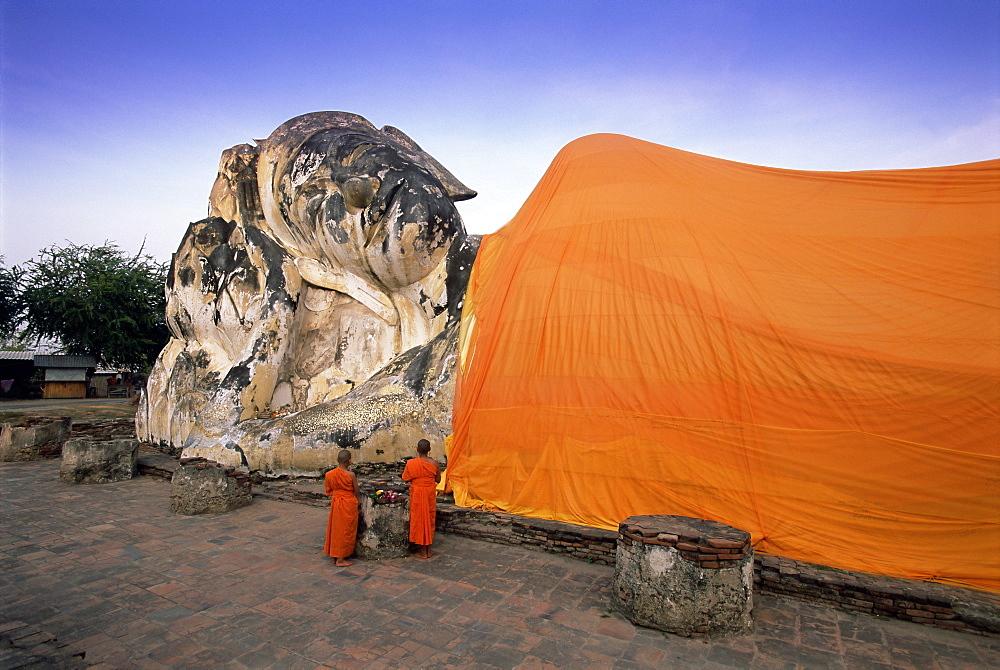 Two novice Buddhist monks in front of a statue of the reclining Budha, Wat Lokayasutharam, Ayuthaya Historical Park, Ayuthaya (Ayutthaya), UNESCO World Heritage Site, central Thailand, Thailand, Southeast Asia, Asia