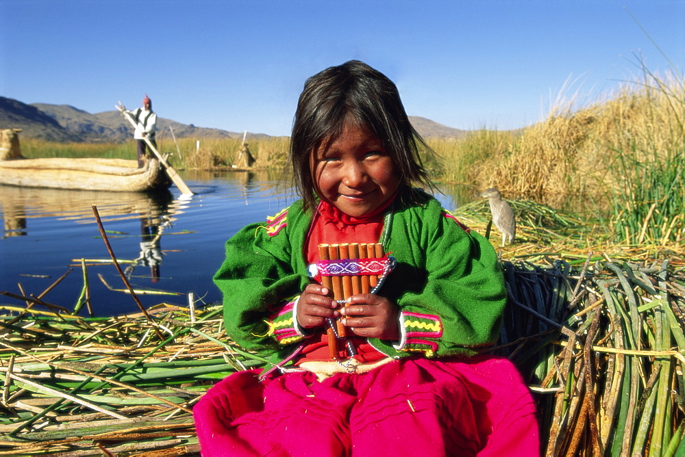 Portrait of a Uros Indian girl holding pan pipes, Islas Flotantes, Lake Titicaca, Peru, South America