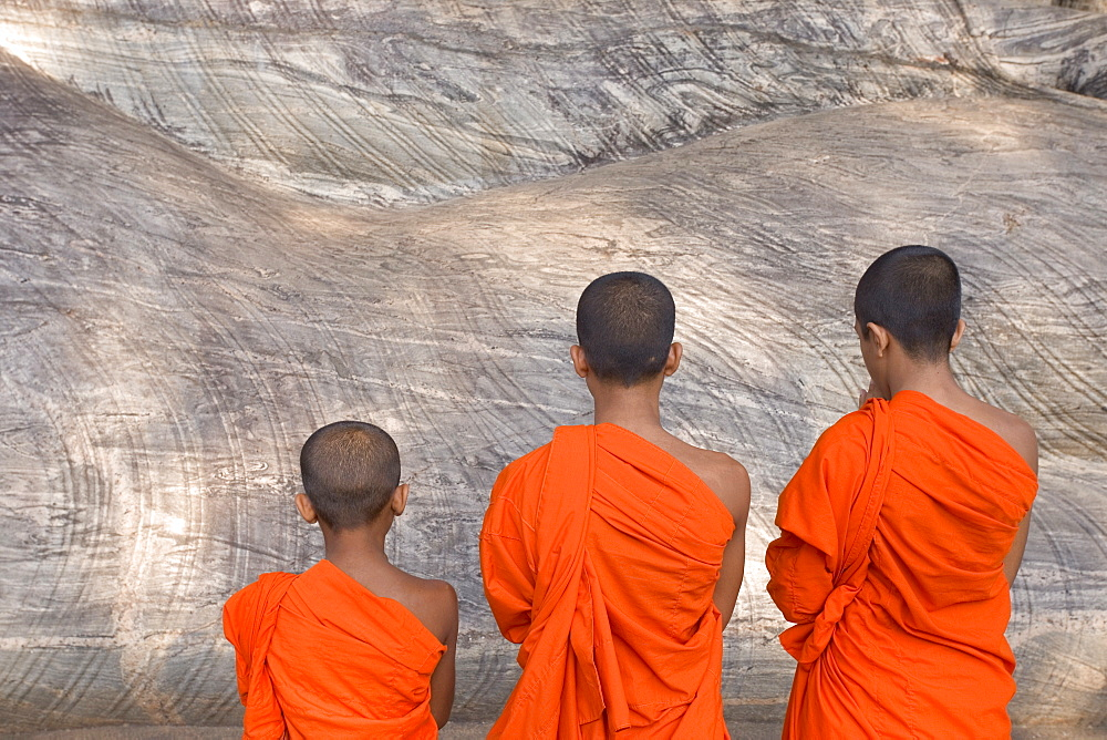 Three young monks praying at a rock-cut image of the Buddha in the Gal Vihara, Polonnaruwa (Polonnaruva), UNESCO World Heritage Site, Sri Lanka, Asia