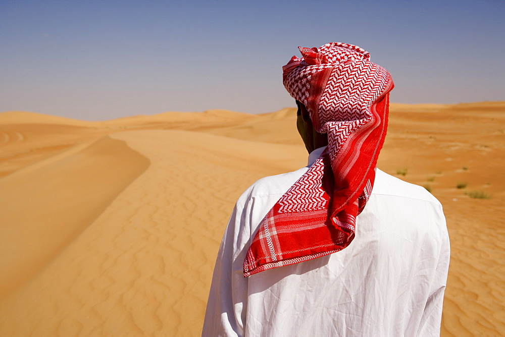 Man in traditional dress in the desert outside Dubai, United Arab Emirates, Middle East