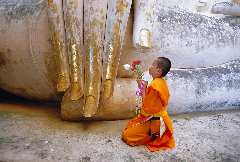 Novice Buddhist monk kneeling beneath the Phra Atchana Buddha statue, Wat Si Chum, Sukhothai, UNESCO World Heritage Site, Sukhothai Province, Thailand, Asia