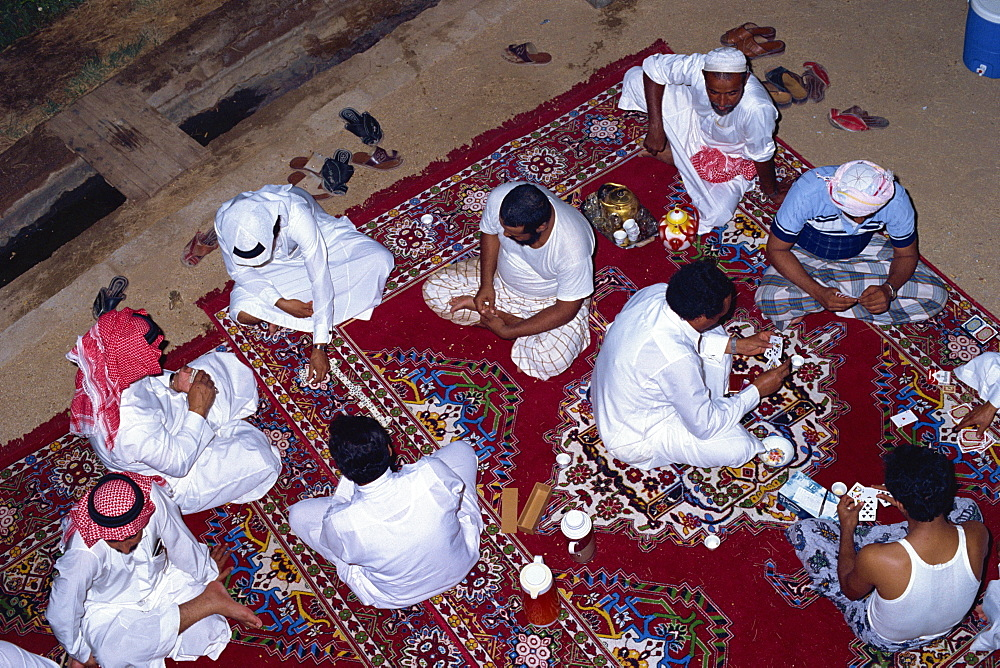 Overhead view of a group of men gathering for tea, cards and dominoes, Saudi Arabia, Middle East