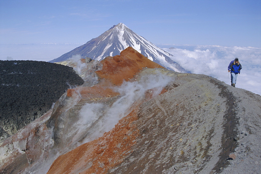 Koryaksky volcano seen beyond walkers on crater rim of Avacha volcano, Kamchatka, East Siberia, Russia