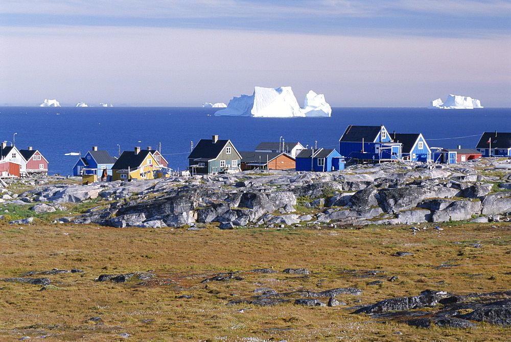 Painted village houses in front of icebergs in Disko Bay, Oeqertarsuaq (Godhavn), Disko island, west coast, Greenland, Polar Regions