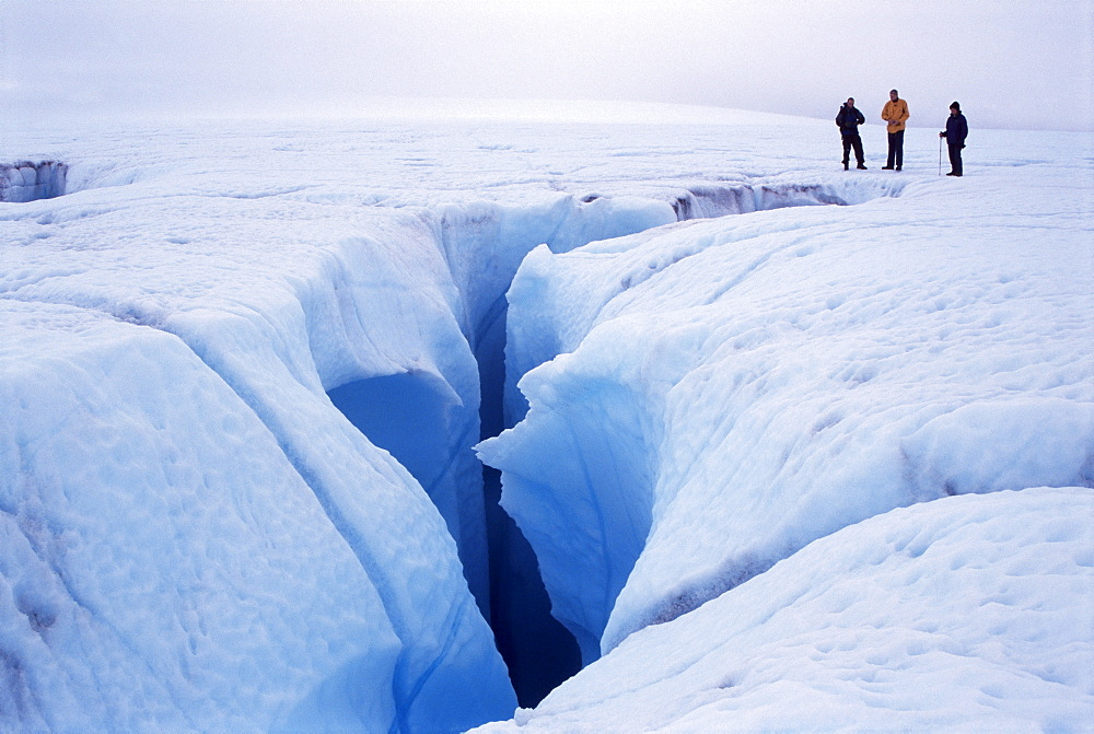 Canyon cut by meltwater stream, before sinking into moulin beside hikers, on icecap above Disko Bay on the west coast, Greenland, Polar Regions