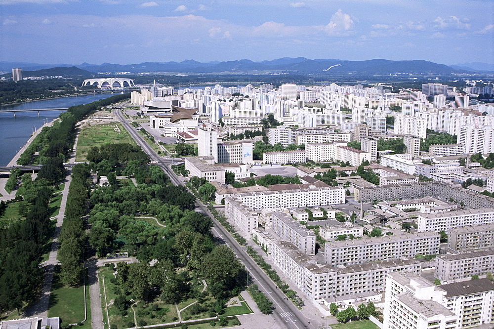 Blocks of flats beside Taedong River, park and distant Mayday Stadium, Pyongyang, North Korea, Asia