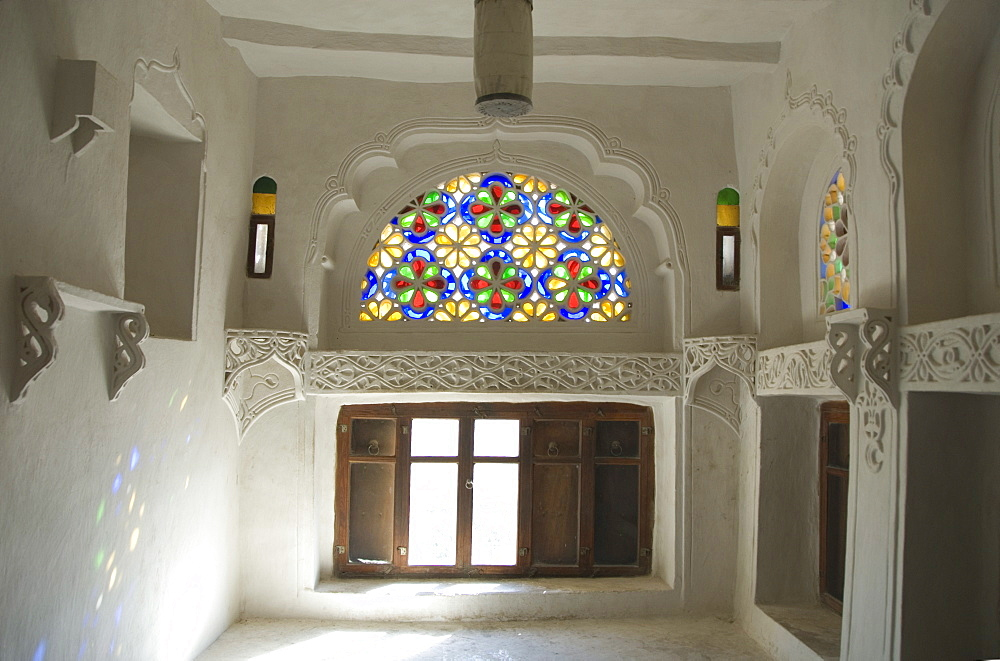 Traditional upper window of stained glass in upstairs room within the Dhar Alhajr (the Iman's Palace), Wadi Dhahr, near Sana'a, Yemen, Middle East