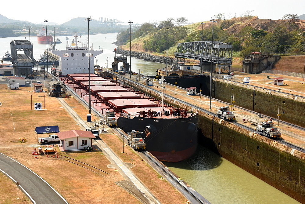 Electric mules guiding Panamax ship through Miraflores Locks on the Panama Canal, Panama, Central America
