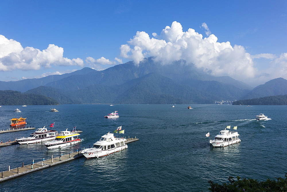 travel destination, photography, horizontal, colour image, horizontal, outdoors, day, cloudy sky, lake, shuishe pier, sun moon lake, taiwan, asia, pier, mountain, blue, elevated view, incidental people, transportation, yacht, taiwanese culture - 306-4412