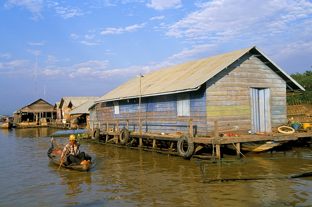 Man in canoe passing a house, floating fishing village of Chong Kneas, Tonle Sap lake, near Siem Reap, Cambodia, Indochina, Southeast Asia, Asia