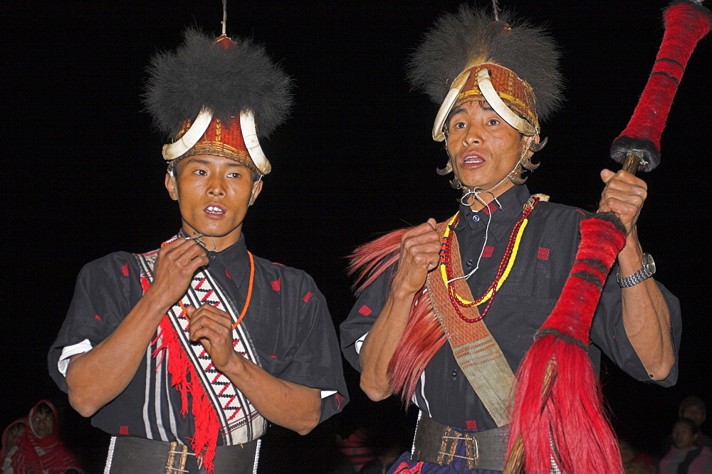 Naga men dancing at Grand Finale wearing headdress made of woven cane decorated with wild boar teeth, Mithan horns (wild cow) and bear fur,  with neckband of tiger claws, Lahe village, Naga New Year Festival, Sagaing Division, Myanmar (Burma), Asia