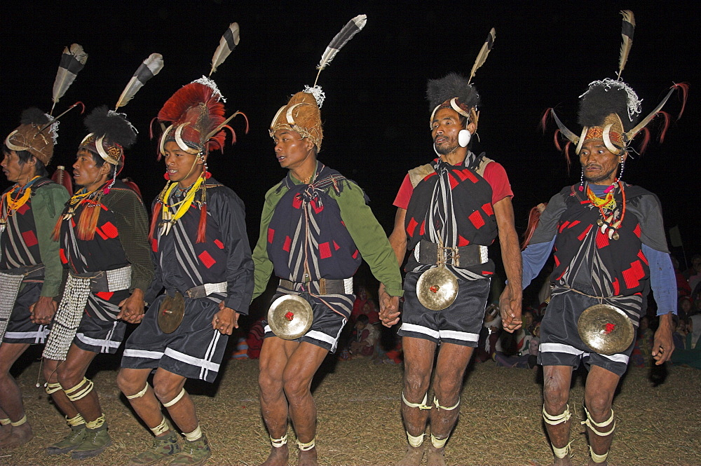Naga men dancing at Grand Finale wearing headdress made of woven cane decorated with wild boar teeth, Mithan horns (wild cow) and bear fur topped with Hornbill feather with Tiger teeth necklaces and conch shell ear ornament, Lahe village, Naga New Year Festival, Sagaing Division, Myanmar (Burma), Asia