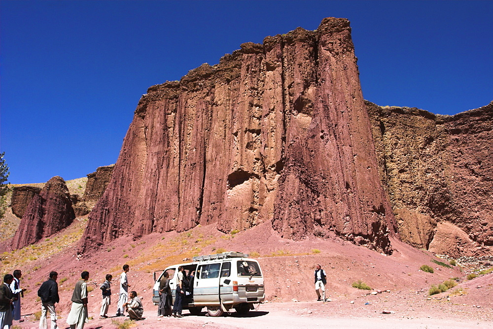 Tourist and locals at the Magenta cliffs near Shahr-e-Zohak (Red City), between Kabul and Bamiyan (the southern route), Bamiyan province, Afghanistan, Asia
