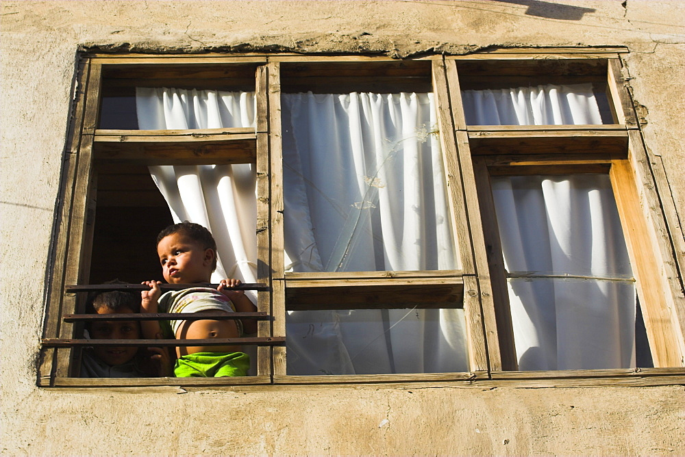 Children looking out of window of old house, Old City, Kabul, Afghanistan, Asia