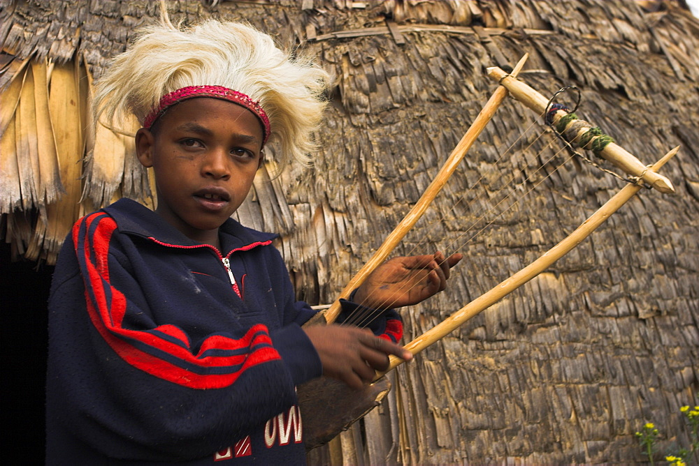 Dorze boy with musical instrument made from bamboo, Chencha mountains, Ethiopia, Africa
