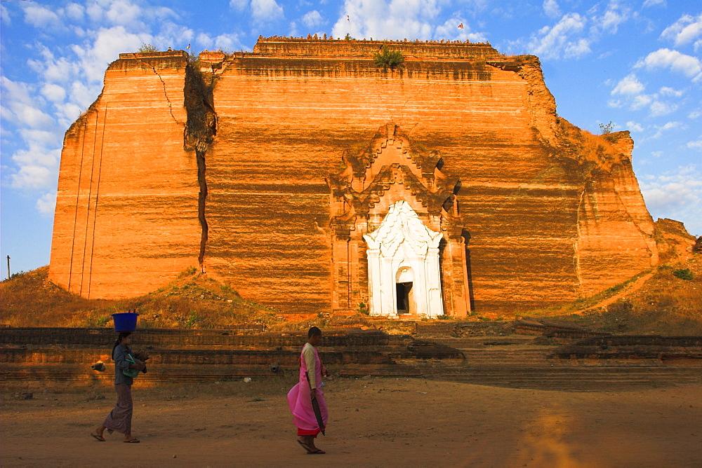Woman and nun walk past paya damaged by earthquakes, Mingun Paya, Mingun, Mandalay, Myanmar (Burma), Asia