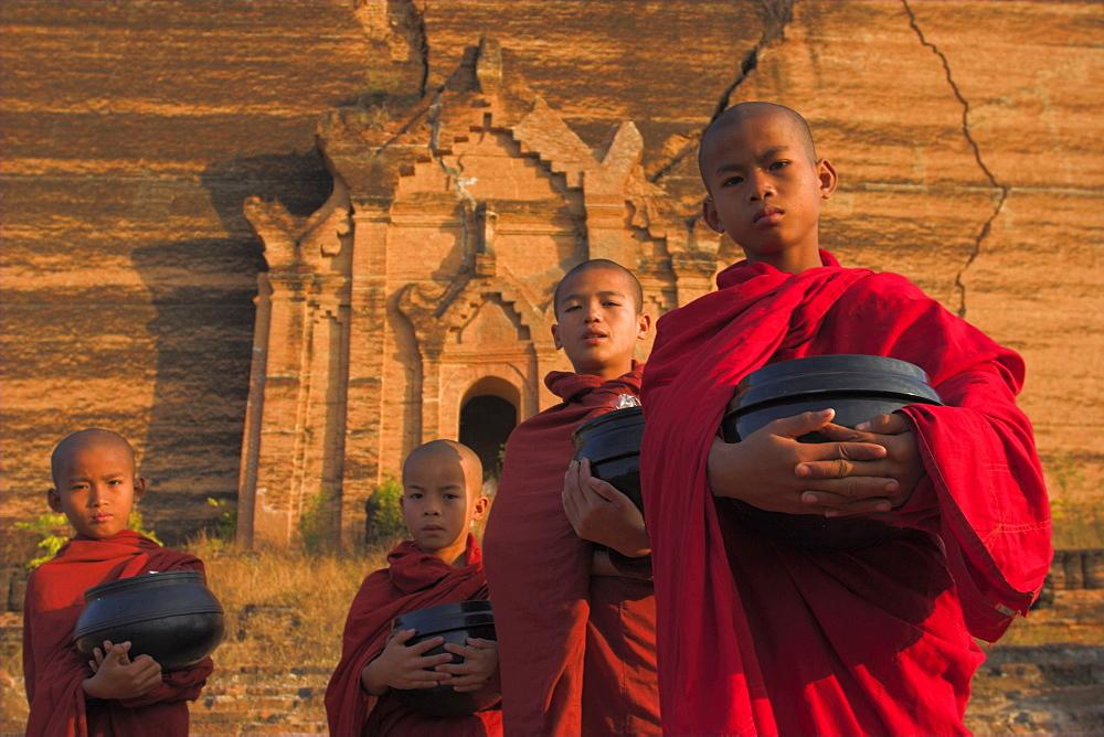 Novice Monks holding alms bowls at Mingun Paya, Mingun, Mandalay, Myanmar (Burma), Asia